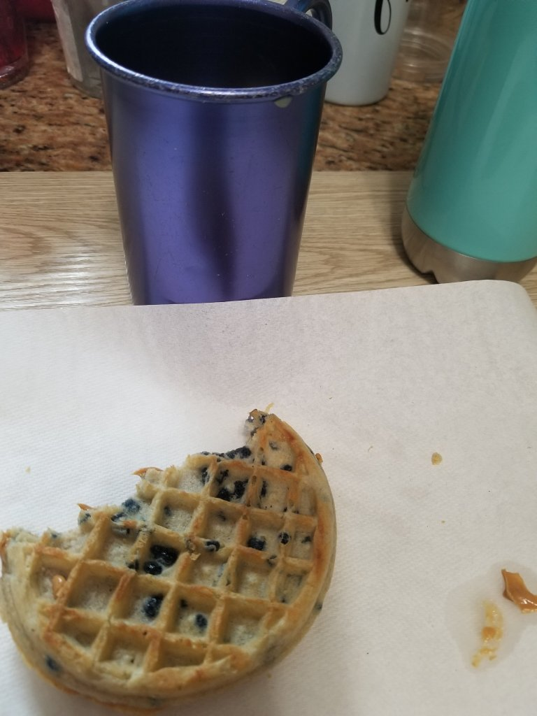 Image shows a half eaten waffle that has peanut butter in it as a sandwich. There is a bronze cup with orange juice in it.