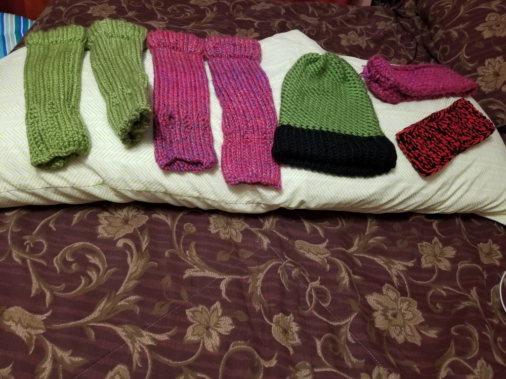 2 sets of long fingerless gloves 1 is green 1 is a purple burgundy  color. There is a green hat with a black brim. There are 2 ear warmers 1 is purple burgundy  and the other is black and red.