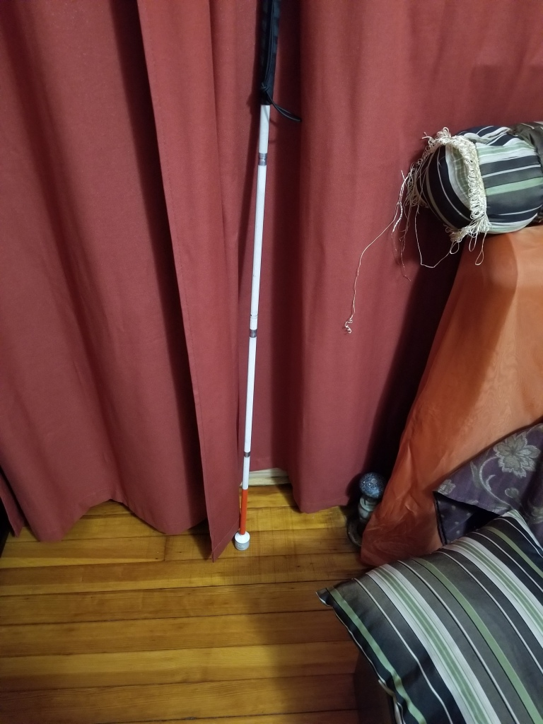 Image is of my white cane leaned against a window that has a curtain over it.