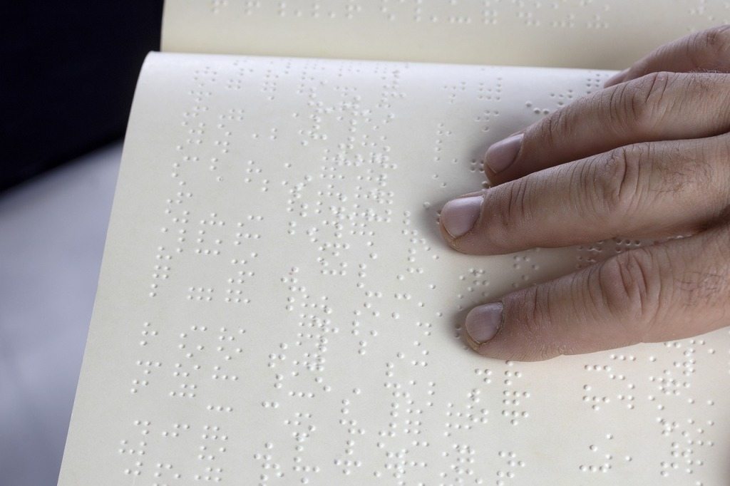 Image shows fingers on a page as a person reads braille.