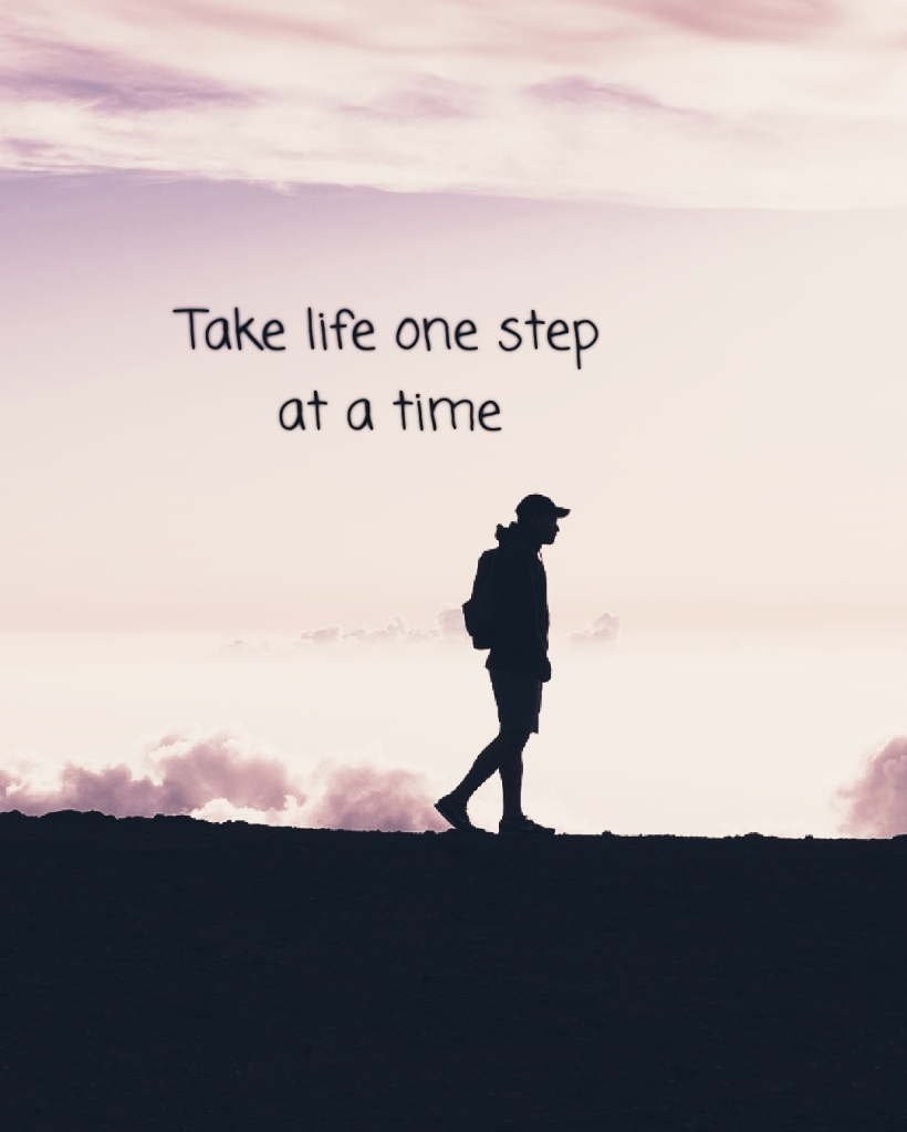 Image shows mountains under a sunny and slightly cloudy sky and a silhouette of a person walking along the path. Text on image reads take life one step at a time