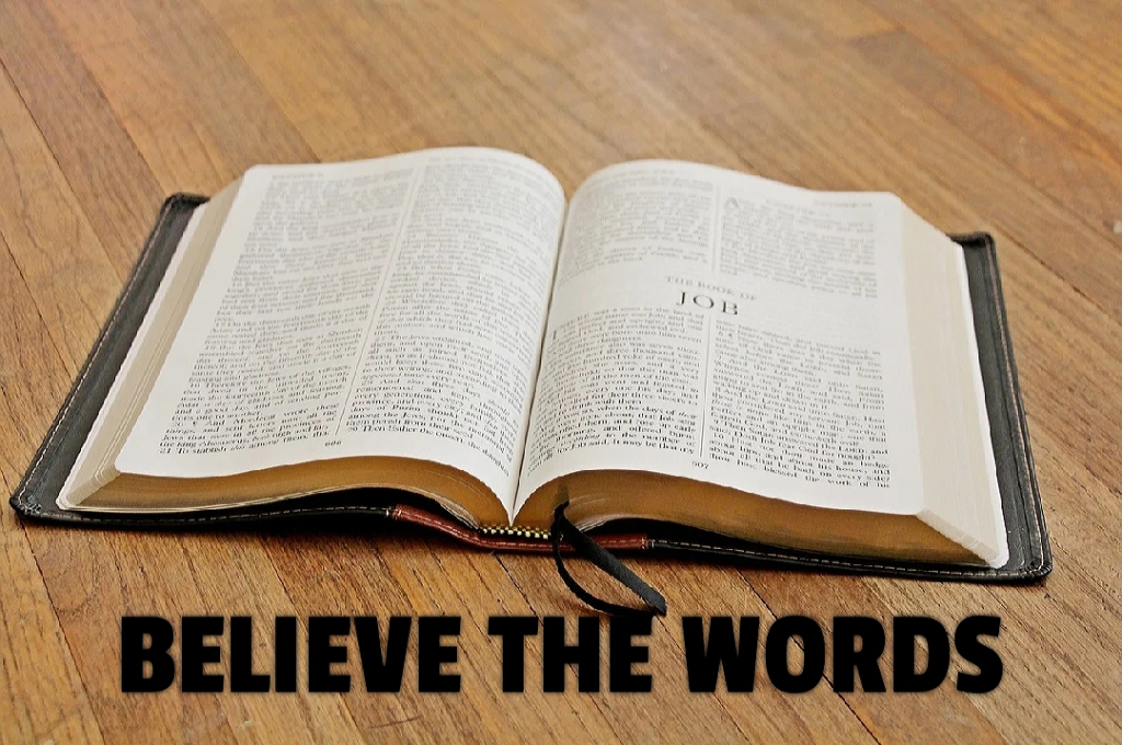 Image shows an open Bible. Text written below the Bible says believe the words.