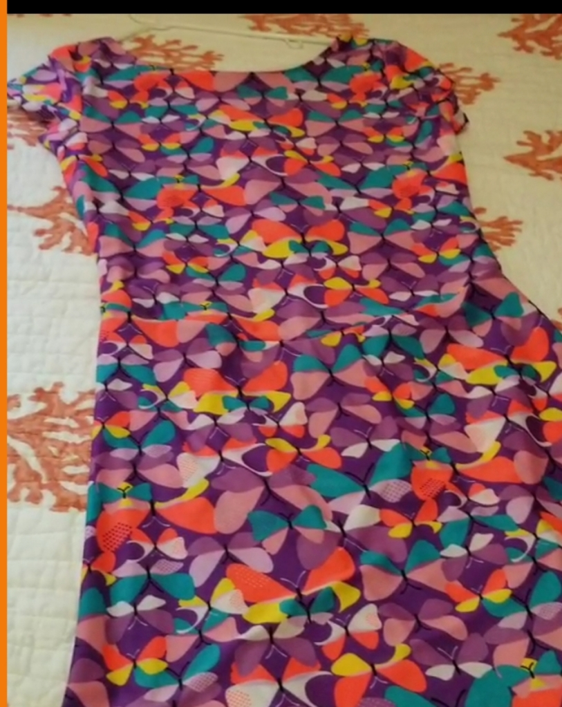 Image description Swim dress from Cute and Covered. The pattern on the dress is of large dots in various colors. They resemble purple butterflies #summer #swimwear #swimsuits