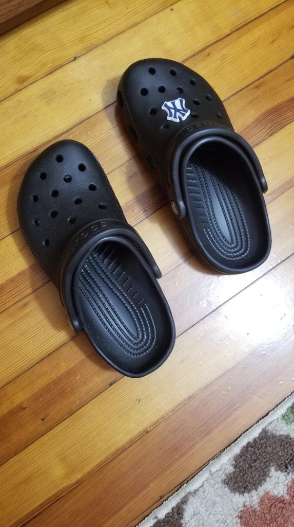 Photo description Black crocks with a New York Yankees jibbit on one shoe #summer #shoes #crocks