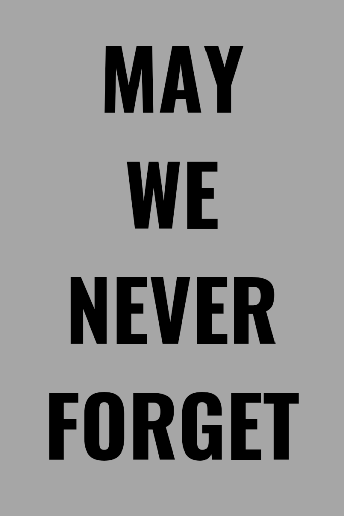 Photo description Text is black and bold in large on a light gray background. Text reads may we never forget