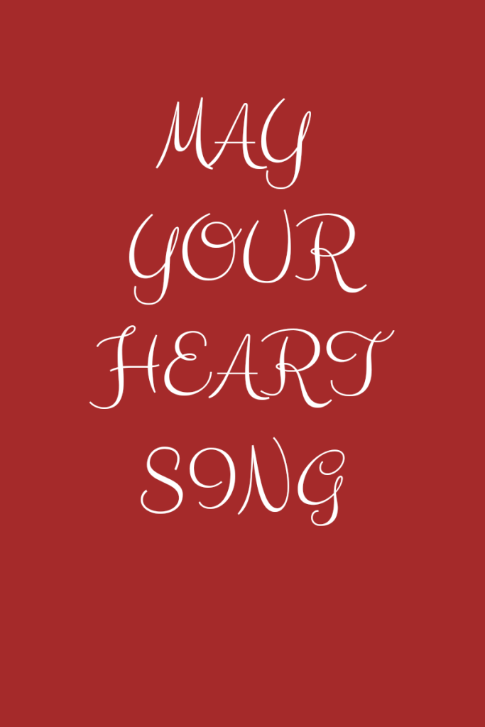 Photo description Text reads may your heart sing. Text is white in script font on a brown background.